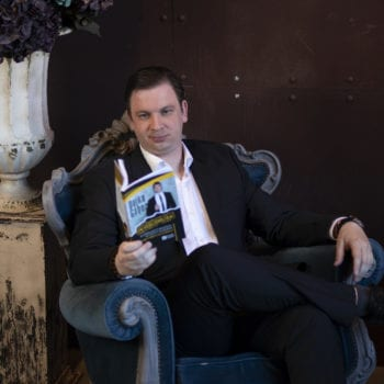 Dajka Gábor öltönyben olvas
