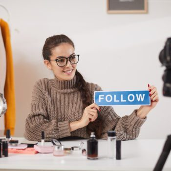 Portrait of contemporary young woman holding FOLLOW word while filming video for beauty and lifestyle channel, copy space
